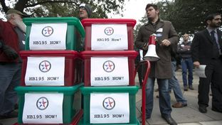 Justin Delosh, r, of Lone Star Gun Rights stands with petitions to be delivered to legislators on the first day of the Texas Legislature on Jan. 13, 2015.