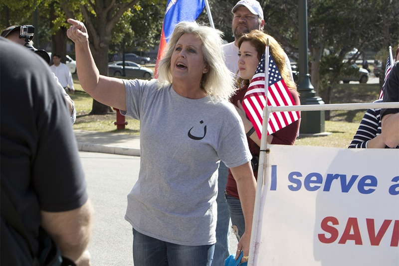 "Protester Christine Weick shouts during the Texas Muslim Capitol Day gathering on Jan. 29, 2015. Weick (identified by the Austin American-Statesman) was later escorted away by DPS troopers after seizing the microphone and disrupting the ceremony. The symbol on her shirt is the Arabic character ""Nun,"" which stands for ""Nazarene."""