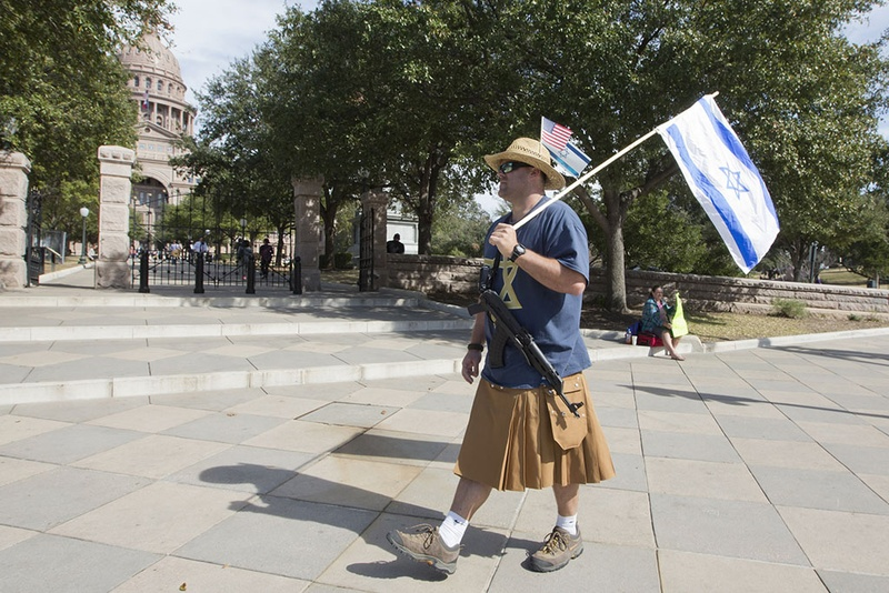 Almost forgotten in the midst of Texas Muslim Capitol Day, an open carry advocate displays his gun and the Israeli flag on Jan. 29, 2015.