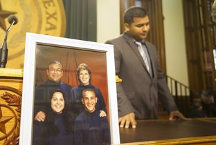 "Erick Muñoz, widow of Marlise Muñoz, speaks at the Texas Capitol after ""Marlise's Law"" was introduced during a press conference on March 12, 2015. A picture of his late wife and her family sits on the table."
