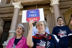 An advocate for restricting funds for toll-roads in Texas attends a rally March 23rd, 2015