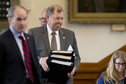 State Rep. John Otto, R-Dayton, carries literature laying out House Bill 1 as he prepares to discuss the appropriations bill on the House floor March 31, 2015.