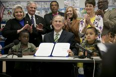 Gov. Greg Abbott signs House Bill 4, which adds funding for pre-kindergarten, into law at the Anita Uphaus Early Childhood Center in Austin on May 28, 2015.