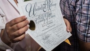 Pamela Holwerds holds up her marriage license following the ceremony that married over 40 same-sex couples on the south lawn of the Texas Capitol in Austin on July 4, 2015.
