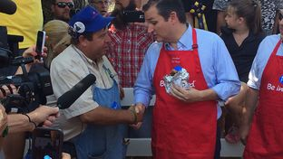 U.S. Sen. Ted Cruz, R-Texas, eats a pork chop sandwich Friday at the Iowa State Fair. Cruz fielded questions throughout his trip to the fair about real estate mogul Donald Trump's controversial immigration proposals.