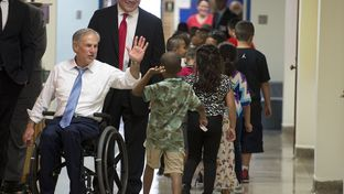 Gov. Greg Abbott greets Zavala Elementary schoolchildren in the hallway of the east Austin school on the first day of classes August 24, 2015.