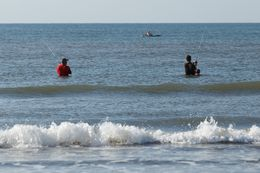 Visitors fish on the shore of Galveston Island State Park.