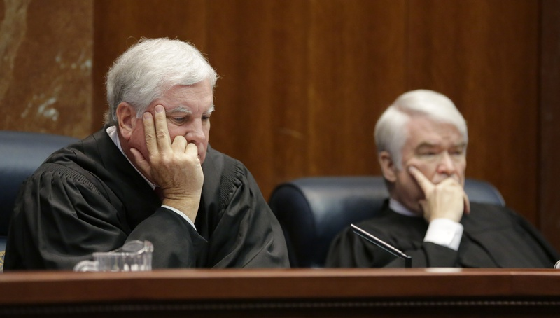 Texas Supreme Court Justices Paul Green, left, and Chief Justice Nathan Hecht listen to oral arguments Sept. 1 in Texas' appeal of a 2014 ruling that struck down its system of funding public schools as unconstitutional.
