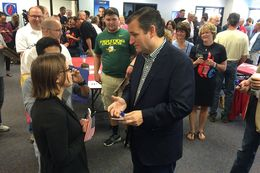 Presidential contender and U.S. Sen. Ted Cruz speaks with a supporter at the opening of his first Iowa office in Urbandale, Iowa on Sept. 26, 2015.