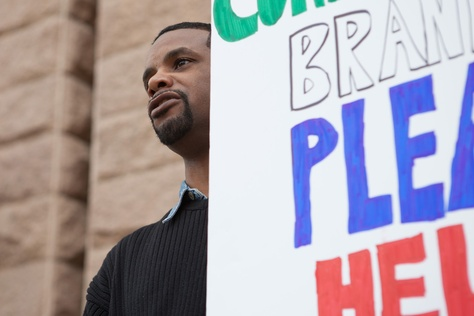 Juan Boston, of Humble, holds a sign in support of injured workers on the steps of the Texas Capitol. The former truck driver has fought a years-long battle for workers' compensation benefits following a back injury that required surgery.