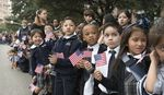 Schoolchildren watch the Veterans Day parade on Congress Avenue on Nov. 11, 2015.
