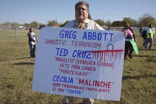 Houston immigration activist Leobardo Santillan holds up a sign in Taylor, Texas on Nov. 19, 2015, during a press conference and rally about immigration reform. Organizers attempted to eject Santillan from the ally but he remained at the event and later joined their march toward Austin.