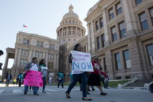 Several pro-immigrant groups march through the Texas Capitol grounds on November 21, 2015