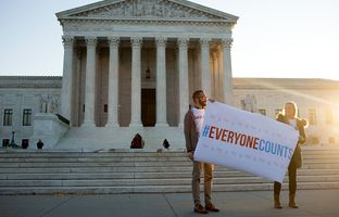 Mario Carrillo (left) and Avery Lord, both of Voto Latino, held a sign ahead of a Congressional Hispanic Caucus prepares press conference in front of the U.S. Supreme Court in Washington, D.C., on Dec. 8, 2015. The Supreme Court heard oral arguments that day in the Evenwel v. Abbott case.