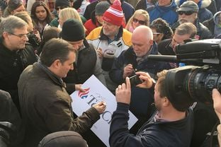 Ted Cruz signs a poster Tuesday after a rally in Hudson, New Hampshire. The Republican presidential candidate returned to the state for the first time in two months.