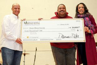State Rep. Dawnna Dukes presents a $20,000 check bearing her signature to Huston-Tillotson University during the 2015 African American Community Heritage Festival.