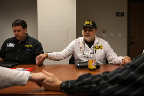 """Michael Tummillo (right), the official volunteer chaplain at the Texas Department of Agriculture,  joins hands in prayer with attendees at a weekly """"Faith at Work"""" gathering at the Stephen F. Austin state office building."""