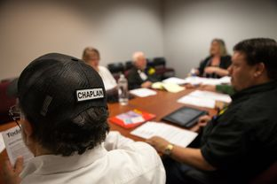 Michael Tummillo, the official volunteer chaplain at the Texas Department of Agriculture, wears his title on his trucker cap.