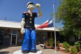 "A statue of Popeye the Sailor stands at the front of the Crystal City City Hall. The struggling South Texas town calls itself the ""Spinach capital of the world."""