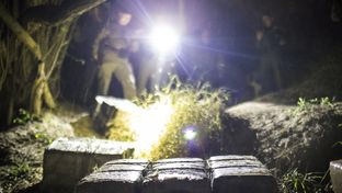 After chasing away smugglers who were using rafts to bring drugs across the river, Border Patrol and Texas DPS agents inspect several large packages of marijuana abandoned near the Rio Grande shoreline. The packages were later found to weigh 313 pounds, making them worth an estimated $240,000 on the street.