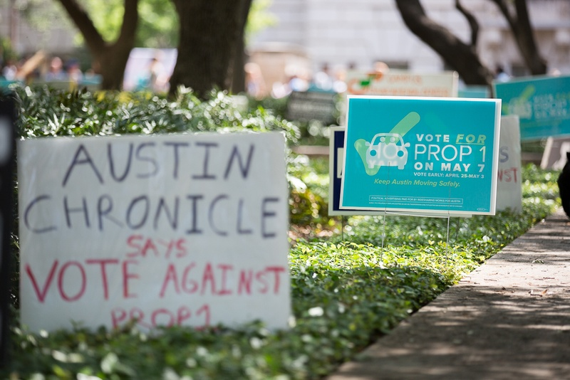 Pro and against signs of Austin's Prop 1 ride-hailing vote posted along voting centers on University of Texas at Austin's campus on April 28, 2016.