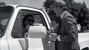 Bruce Jones, president of Perryton-Ochiltree Chamber of Commerce, offered a sip of a non-alcoholic sparkling beverage to a man from Woodward, Okla., on June 16, 1987. The driver was passing by during a town celebration of rising oil prices.