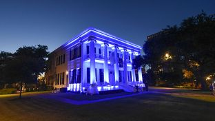 The Texas Governor's Mansion is bathed in blue light at sunset July 8, 2016 as Texans honor five slain police officers in overnight violence in Dallas.  Several other officers were injured along with two bystanders in a shooting melee following a Black Lives Matter march downtown.
