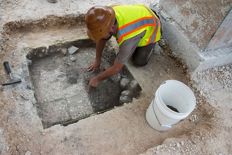 An archaeologist points to recently-discovered Spanish colonial era adobe bricks.