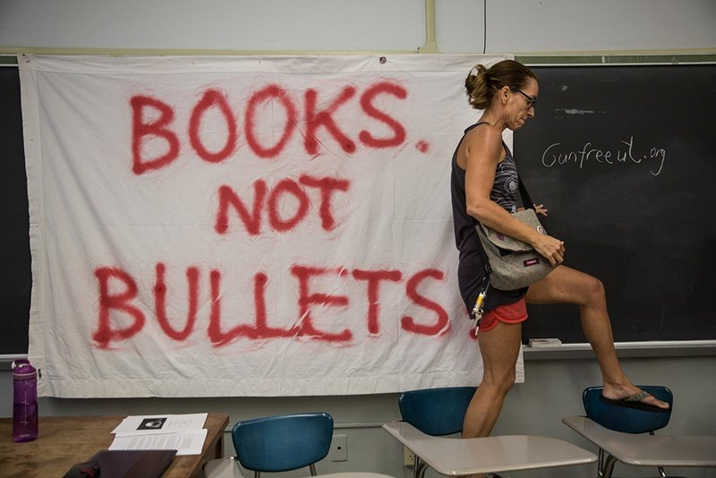 "Pascale Bos, an associate professor at UT Austin, walks over desks after pinning up a ""Books not bullets"" sign at a peace and wellness workshop organized by Gun-Free UT and held in a UT Austin classroom on Aug. 1, 2016, the day Texas' ""campus carry"" law went into effect and the 50th anniversary of the mass shooting that occurred on the UT campus."