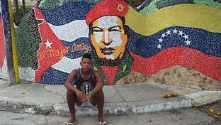 Yasmanny Alcantara, 20, sits in front of a mural near the home of Cuban artist Jose Fuster.