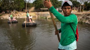 Esvin Lopez, 19, a raft conductor who works ferrying people and goods across the Suchiates River separating Ciudad Hidalgo, Mexico, and Tecun Uman, Guatemala, uses a long wooden pole to propel the raft from one side of the river to the other.