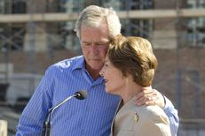 Former President George W. Bush hugs Laura Bush at the topping out ceremony for the George Bush Presidential Center at Southern Methodist University on October 3, 2011.