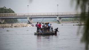 Rafts made of inflatable tires and wooden slats ferry people and goods across the Suchiate River separating Ciudad Hidalgo, Mexico, and Tecun Uman, Guatemala, with the international bridge connecting the two countries in the background.
