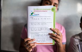 "A student presents her answers to gang related questions in an El Salvador elementary school workbook. ""What have you heard recently about gangs and violence?"" the question asks. ""That there are a lot of murders"" reads the student's response."