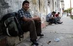 Henri Ávila, a Guatemalan manual laborer, waits for a bus to take him to work in Mexico.