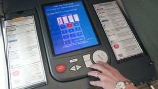 An election judge in south Texas tests a voting machine for accuracy after early voting hours ended on October 26, 2016.
