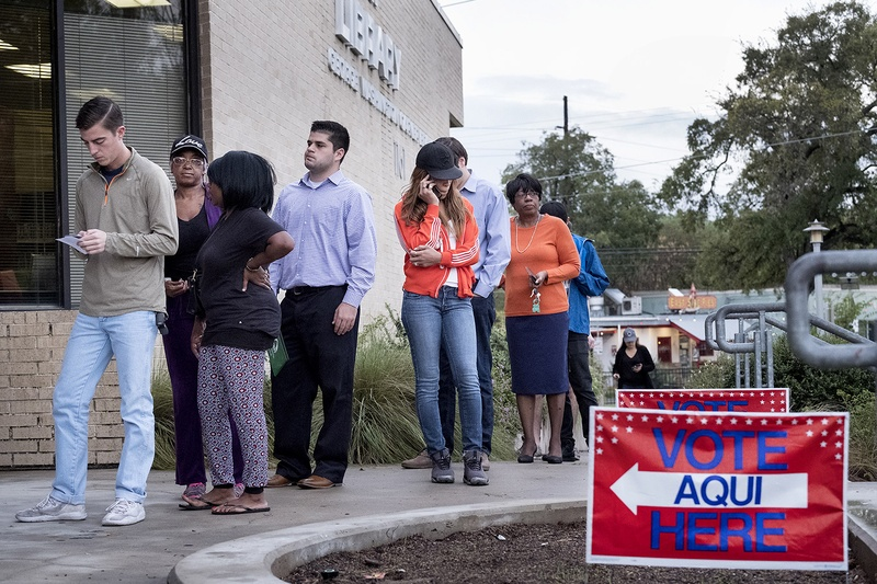 People wait in line at the George Washington Carver Library in Austin, Texas, to cast their vote on Election Day 2016.