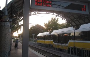 A Dallas Area Rapid Transit train headed south on the Red Line stops at Hampton Station as an electronic message board announces the arrival time for northbound trains in October 2016.