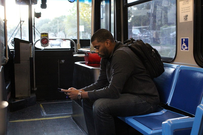 Houston resident Chase Floyd  focuses on his phone while taking Houston METRO's Route 20 bus home from work.