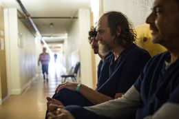 Patients sit on a bench in the hallway of the detox wing at Charlie's Place Recovery Center in Corpus Christi.
