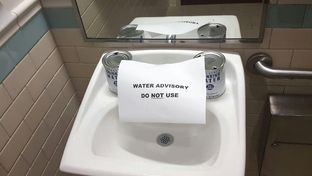 A sign posted at a sink at a Corpus Christi-area health clinic on the morning of Dec. 15, 2016.  City officials announced a ban on using the city's water the evening before due to a chemical making its way into the supply.