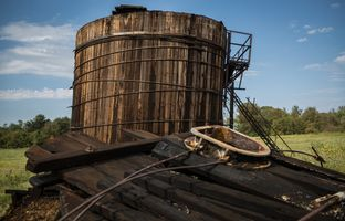 A long-abandoned oil tank battery stands next to debris from a collapsed tank battery on a Luling ranch owned by Stuart Carter. The leftover oil that coats the wood sometimes blackens the heads of his cattle.