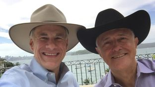 Gov. Greg Abbott and Australian Prime Minister Malcolm Turnbull show off hats they exchanged after their meeting Tuesday in Sydney. Abbott was vacationing with his family in the city.