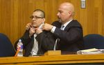 Lead defense attorney Carlos Garcia assists defendant Joel Luna in putting on a tie prior to Luna's murder trial in Brownsville on January 17, 2017.