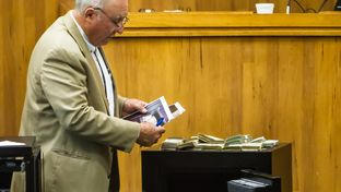 Chief Prosecutor Gus Garza examines a safe and cash seized from Border Patrol Agent Joel Luna's mother-in-law's home, during Luna's murder trial on Jan. 20, 2017 in Brownsville.