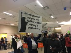 A protester holds a sign at D/FW airport Saturday.