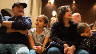 Syrian refugee family Abdul Ghani (left), his wife Sana Alaama (second from right) and their daughters, Laila Alaama (second from left) and Sama Alaama, attend a vigil at the First English Lutheran Church in Austin on Jan. 30, 2017.