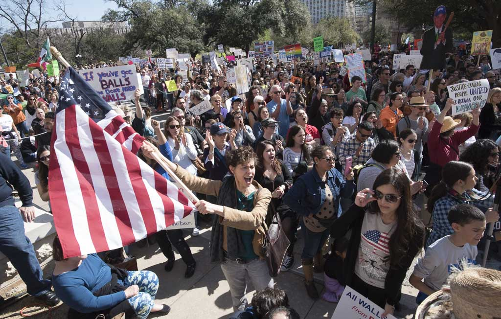 Dorothy Kuhn waves the American flag before thousands gathered at the South Steps of the Texas Capitol on Feb. 25, 2017 for a #NoBanNoWall rally decrying Trump's immigration policies.