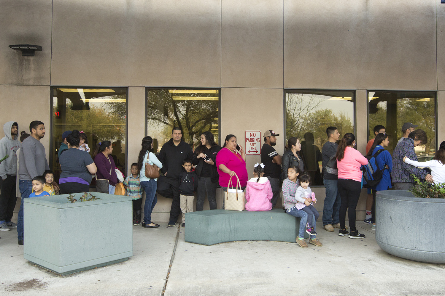 Families wait in line outside Travis County's passport office. Undocumented parents fearing deportation visited the office to get passports for their American children.