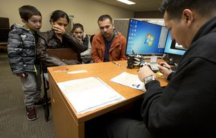 Deputy District Clerk Erik Ortiz begins to process passport application paperwork for the children of Carlos Bernal and Noralia Arroyo, who stood in line for hours at the Travis County District Clerk's office, on Feb. 27, 2017.